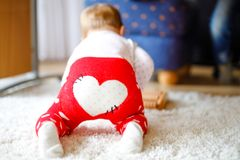 Little cute baby girl learning to crawl. Healthy child crawling in kids room with colorful toys. Back view of baby legs. Cute toddler discovering home and stock photos