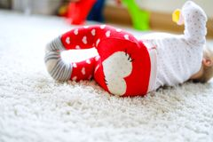 Little cute baby girl learning to crawl. Healthy child crawling in kids room with colorful toys. Back view of baby legs. Cute toddler discovering home and royalty free stock photography