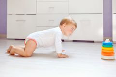 Little cute baby girl learning to crawl. Healthy child crawling in kids room. Smiling happy healthy toddler girl. Cute. Toddler discovering home and learning stock photo