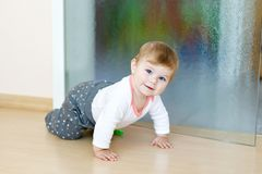 Little cute baby girl learning to crawl. Healthy child crawling in kids room. Smiling happy healthy toddler girl. Cute. Toddler discovering home and learning stock photos
