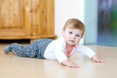 Little cute baby girl learning to crawl. Healthy child crawling in kids room. Smiling happy healthy toddler girl. Cute. Toddler discovering home and learning royalty free stock image