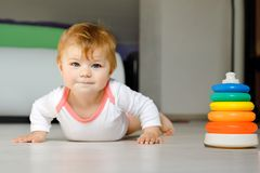 Little cute baby girl learning to crawl. Healthy child crawling in kids room. Smiling happy healthy toddler girl. Cute. Toddler discovering home and learning royalty free stock images