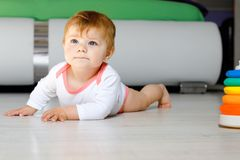 Little cute baby girl learning to crawl. Healthy child crawling in kids room. Smiling happy healthy toddler girl. Cute royalty free stock photo