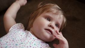Baby girl lies on the floor, smiles and starts to get up in slow motion stock video footage