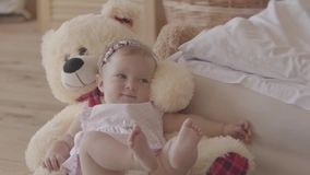 Little baby girl in a pink dress and diaper lying on the bear toy on the bed at home, raising feet up. Concept of a stock video footage