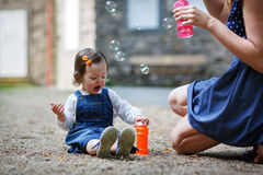 Little cute baby girl playing with soap bubbles in summer park Stock Photography