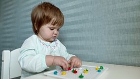 Baby girl sits at a childs table and collects a mosaic close up in slow motion