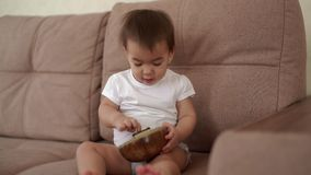 Little baby girl sitting on the couch and playing a musical instrument Kalimba. Little cute baby girl sitting on the couch and playing a musical instrument stock video