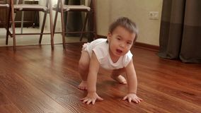 Little cute baby girl stand up to its feet in slow motion stock video footage