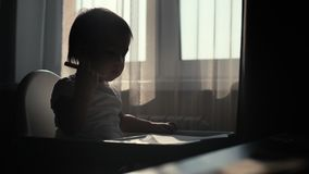 Little cute baby girl takes a pencil and starts drawing on paper stock footage