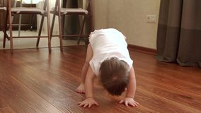 Little cute baby girl trying to stand on her own feet in slow motion stock video footage