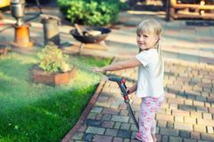 Little cute baby girl watering fresh green grass lawn mear house backyard on bright summer day. Child having fun playing. Little cute baby girl watering fresh royalty free stock photography