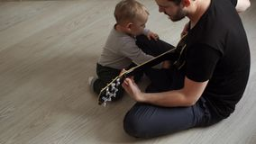 Little cute baby listens curiously as his father plays the guitar stock footage