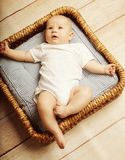 Little cute baby lying in basket Stock Photo