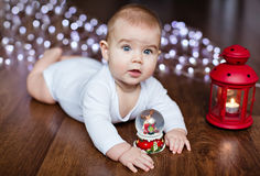 Little cute baby lying on the wooden floor on the background of stock image