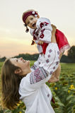Little cute baby in national dress with sunflower. Stock Images