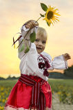 Little cute baby in national dress with sunflower. Royalty Free Stock Photos