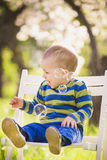 Little cute baby playing with soap bubbles. Adorable boy sitting on white wooden chair outdoors at spring blossom of apple trees background Stock Images
