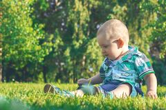 Little cute baby siting in the grass. Lifestyle, fashion and trendy style. Advertising clothes. Summer collection. Little cute baby siting on the grass and Stock Image
