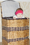 Little cute baby sits in big wicker basket Royalty Free Stock Images