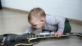 Little cute baby studying guitar with curiosity. Little cute baby is studying the guitar with curiosity on the floor stock footage