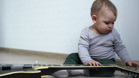 Little cute baby trying to play guitar stock video footage