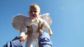 Little cute baby with white angel wings rised up in parent hands to blue sky stock footage