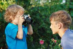Little cute blond boy with a camera shoots brother stock photography