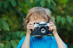 Little cute blond boy with a camera shoots you Royalty Free Stock Photos
