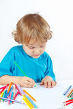Little cute blond boy draws with color pencils Royalty Free Stock Image