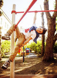 Little cute blond boy hanging on playground outside, alone train Stock Images