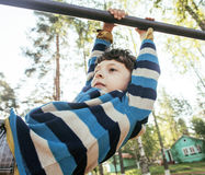 Little cute blond boy hanging on playground outside, alone training with fun, lifestyle children concept Stock Photography