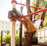 Little cute blond boy hanging on playground outside, alone training with fun, lifestyle children concept Stock Images
