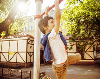 Little cute blond boy hanging on playground outside, alone training with fun, lifestyle children concept Stock Photos