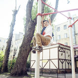 Little cute blond boy hanging on playground outside, alone training with fun, lifestyle children concept Royalty Free Stock Photos