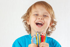 Little cute blond boy holds color pencils Stock Photo