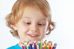 Little cute blond boy looks on color pencils Royalty Free Stock Photo