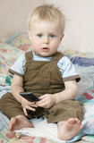 Little cute blond boy one years old. Little cute blond serious boy one years old playing  with mobile phone sitting on bed Royalty Free Stock Photo