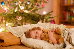 Little cute blond boy sleeping under Christmas tree. And dreaming of Santa at home, indoors Stock Images
