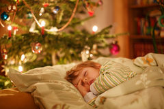 Little cute blond boy sleeping under Christmas tree Stock Images