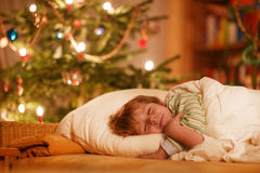 Little cute blond boy sleeping under Christmas tree Stock Photography