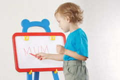 Little cute blond boy wrote the word mum Royalty Free Stock Photos