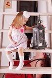 Little cute blond girl in dress sitting on stairs with wi Stock Photos