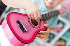 Little cute blond girl having fun learning to play small ukulele guitar at home.Toddler girl playing toy musical. Instrument indoors stock image