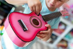 Little cute blond girl having fun learning to play small ukulele guitar at home.Toddler girl trying to play toy musical stock photo