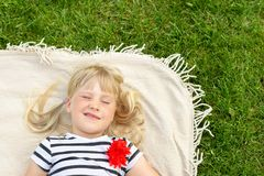 Little cute blond girl lying on blanket over green grass lawn and smiling. Adorable child having fun outdoors. Happy stock images