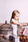 Little cute blond girl sitting in room and playing with toys and Royalty Free Stock Photo