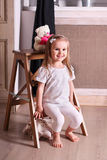 Little cute blond girl sitting on small wooden ladder in room wi Royalty Free Stock Photo