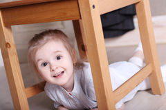 Little cute blond girl in striped shirt on floor under stool Stock Photography