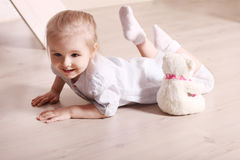 Little cute blond girl in striped shirt is smiling on floor with Royalty Free Stock Photography